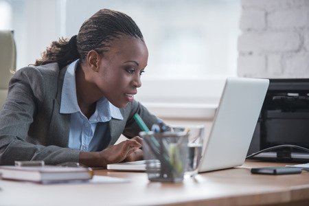 white collar worker: Pretty african business woman working on laptop in office