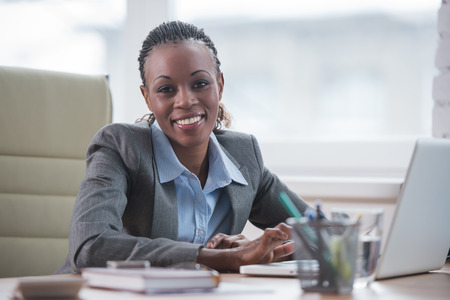 attractive office: Pretty cheerful african businesswoman working with laptop in office and looking at camera