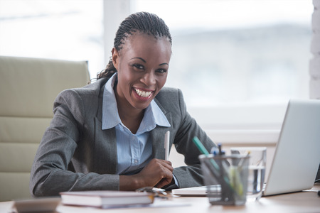 business woman: Pretty cheerful african businesswoman working with laptop in office and looking at camera