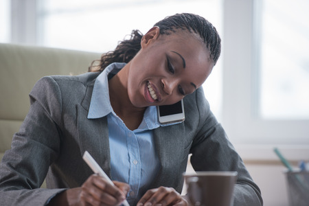 woman with document: Portrait of businesswoman working with laptop writes on a document and calling phone at her office
