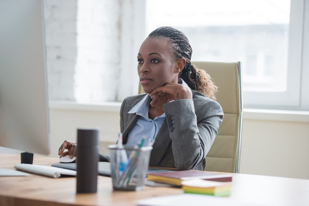 Beautiful young african american businesswoman working on computer at office