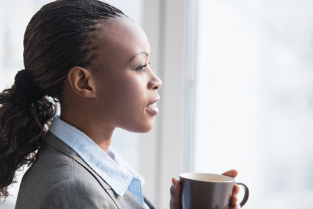 business lifestyle: Pretty african businesswoman standing near window and drinking coffee or tea while resting and thinking about something Stock Photo