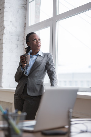female: Happy african business woman enjoying the coffee break at her office and looking at window