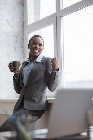 mujer trabajadora: Retrato de sonriente mujer de negocios africano en su oficina con la taza de caf� que celebra �xito y expresando alegr�a felicidad y positivismo