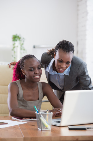working on school project: Young african business women in office working together on laptop