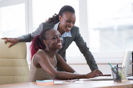 oficina: Mujeres de negocios africanas jovenes en oficina trabajando juntos en la computadora port�til