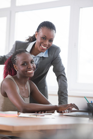 Young african business women in office working together on laptop photo