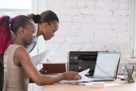 Jonge Afrikaanse zakenvrouwen in kantoor samen te werken op laptop Stockfoto