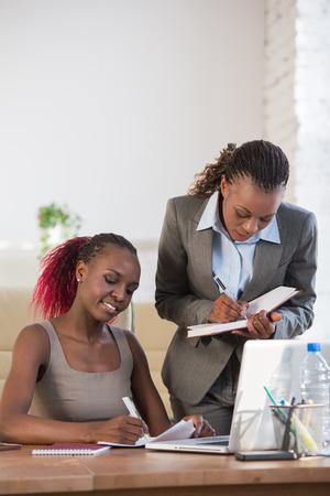 mujeres africanas: Dos alegres mujeres de negocios afroamericano que trabajan en la oficina en un ordenador