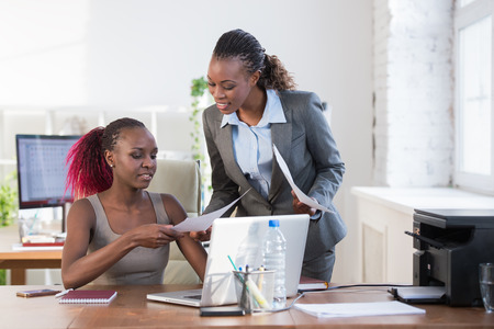Twee vrolijke Afro-Amerikaanse zakelijke vrouwen werken op kantoor op een computer Stockfoto