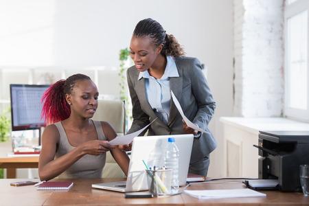 black girl: Zwei fr�hliche African American Business-Frauen arbeiten im B�ro auf einem Computer Lizenzfreie Bilder