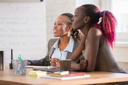 using the computer: Imagen de dos mujeres de negocios africanos j�venes que usan el ordenador en la reuni�n