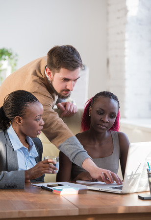 Image of group of three young business people using laptop at meeting photo