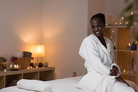 Jonge mooie Afrikaanse vrouw zitten aan beauty spa salon draagt een badjas