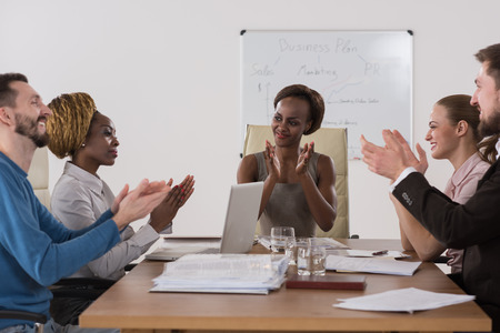 Photo of happy business people applauding at meeting focus on boss african girl photo