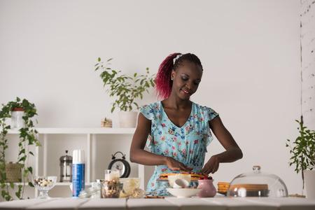 famille africaine: Jeune femme Cuisiner à la maison.
