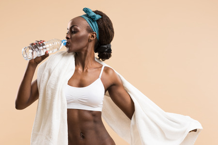 water aerobics: Sporty african woman drinking water from bottle. Fit sexy body