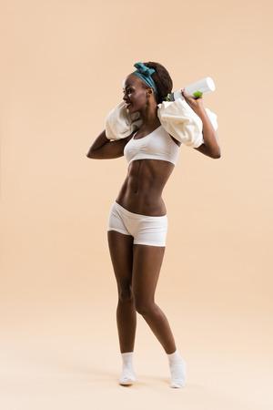 sexy young girl: Спортивное африканского девушка с бутылкой воды и полотенце Фото со стока