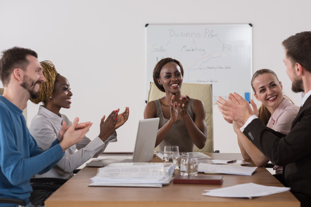 Foto van gelukkige mensen uit het bedrijfsleven applaudisseren tijdens de vergadering focus op baas Afrikaans meisje