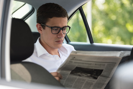 financial newspaper: Businessman reading news in his car