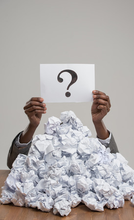 imploring: African business woman under crumpled pile of papers with hands holding a question sign