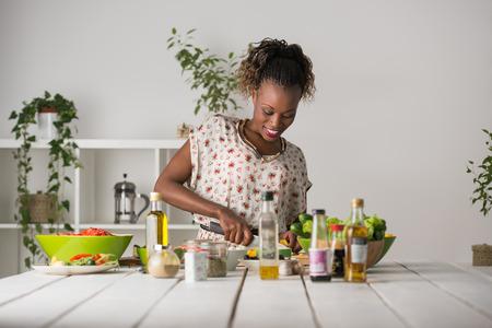 cocineros: Joven mujer cocina africana. Alimentación saludable - ensalada de verduras. Dieta. Concepto de dieta. Estilo de vida saludable. Cocinar en casa. Preparar Alimentos