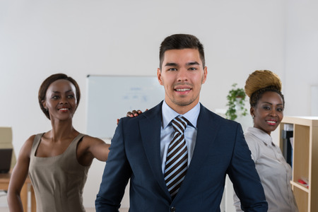 multi ethnic: Team leader stands with coworkers in background. Multi ethnic group of people