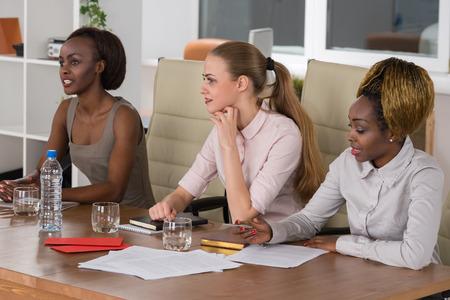 Grupo mezclado en la reunión de negocios sólo mujeres