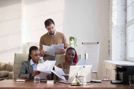 Image of group of three young business people of different ethnicity working together photo