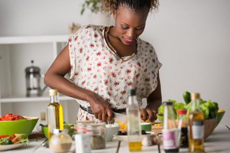 femme africaine: Jeune femme cuisine africaine. Alimentation saine - salade de légumes. Diète. Régime amaigrissant Concept. Mode de vie sain. Cuisiner à la maison. Préparer les aliments