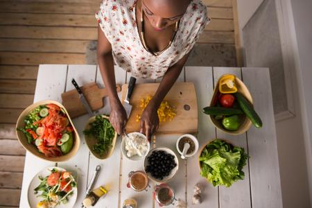 modelos negras: Joven mujer cocina africana. Alimentaci�n saludable - ensalada de verduras. Dieta. Concepto de dieta. Estilo de vida saludable. Cocinar en casa. Preparar Alimentos. Vista superior