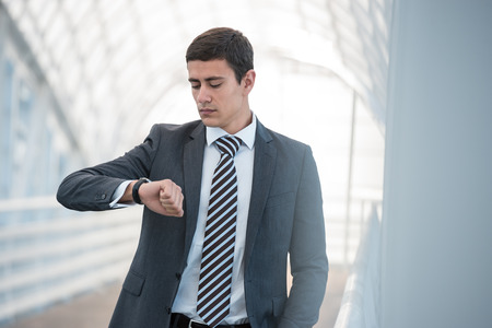 go inside: Businessman looking at watches while walking outside modern building