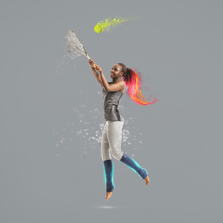 Full length portrait of young african woman playing tennis bright collage with fire and splashes photo