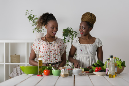 two friends talking: Two Young African Women Cooking. Healthy Food - Vegetable Salad. Diet. Dieting Concept. Healthy Lifestyle. Cooking At Home. Prepare Food Stock Photo