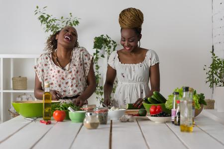 Twee Afrikaanse vrouwen koken in de keuken het maken van gezonde voeding salade met groenten Stockfoto