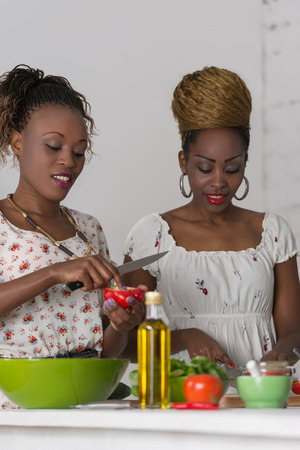 Two african women cooking in kitchen making healthy food salad with vegetables photo
