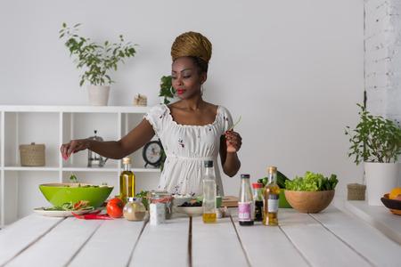 aceite de cocina: Mujer africana sonriente cortar las verduras para la ensalada en la cocina