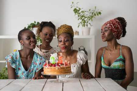 black hands: Portrait of joyful african girl looking at birthday cake surrounded by friends at party