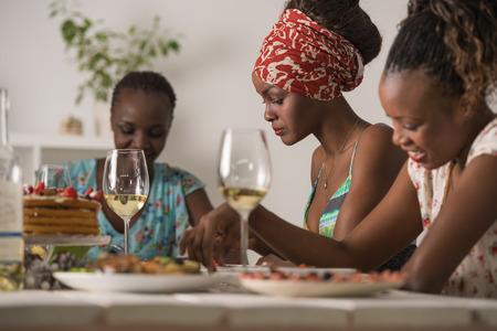 alimentos y bebidas: Grupo de Amigos femeninos que disfrutan de la comida en casa