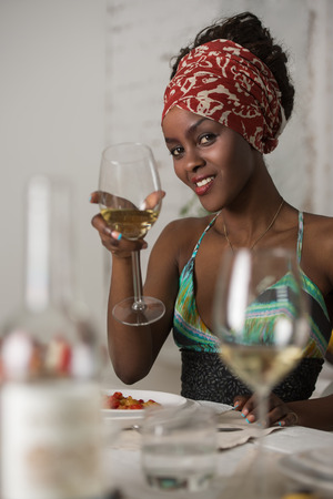native american girl: African woman eating at home and drinking wine and looking very happy