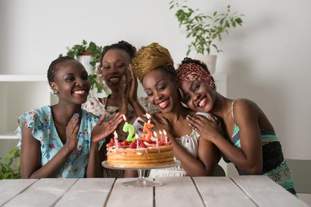 Portret van vreugdevolle Afrikaanse meid kijken naar verjaardagstaart omringd door vrienden op feest Stockfoto