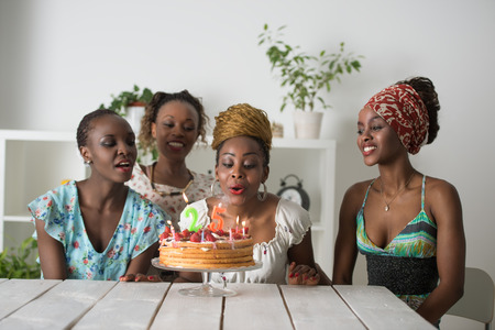 surrounded: Portrait of joyful african girl looking at birthday cake surrounded by friends at party