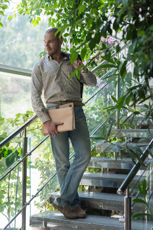 Handsome confident businessman portrait standing on stairs and holding documents photo