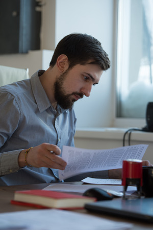 busy beard: Handsome businessman signing contract in office