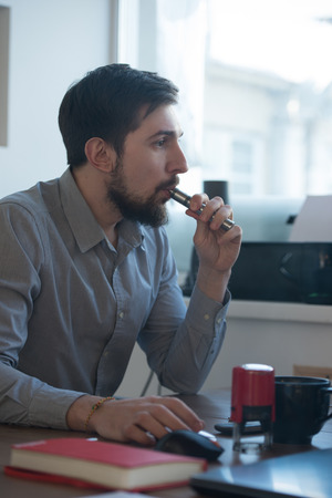 Handsome businessman working with computer in office and vaping electronic cigarette