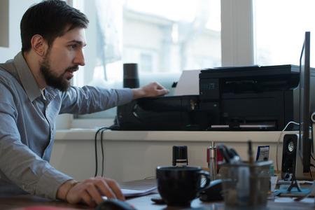 documentos: Exploraci�n Apuesto hombre de negocios y de documentos de impresi�n en la oficina