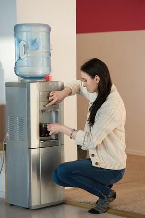Jonge vrouw met behulp van water dispenser op het kantoor Stockfoto
