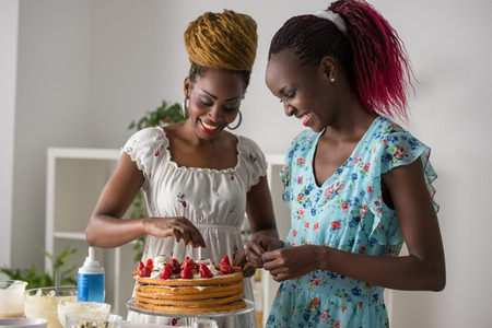 women friends: Young african women at the kitchen cooking cake with strawberry Stock Photo