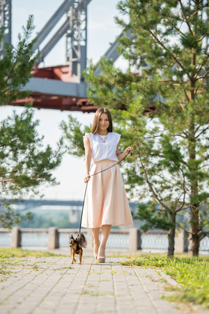 walk in the park: Young beautiful lady walking with her dog on lead in summer park Stock Photo