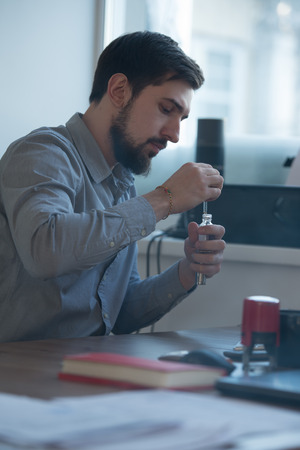 busy beard: Handsome businessman filling electronic cigarette with liquid in office Stock Photo